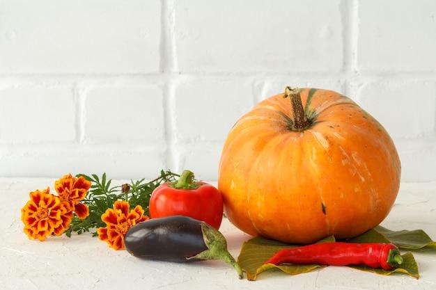 Herbstkomposition mit einem großen kürbis und gemüse. kürbis und paprika, paprika und blumen auf weißem hintergrund. herbst einkaufen. erntedankfest.