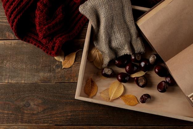 Herbstkomposition mit einem schal und einem tablett auf einem braunen hölzernen hintergrund.