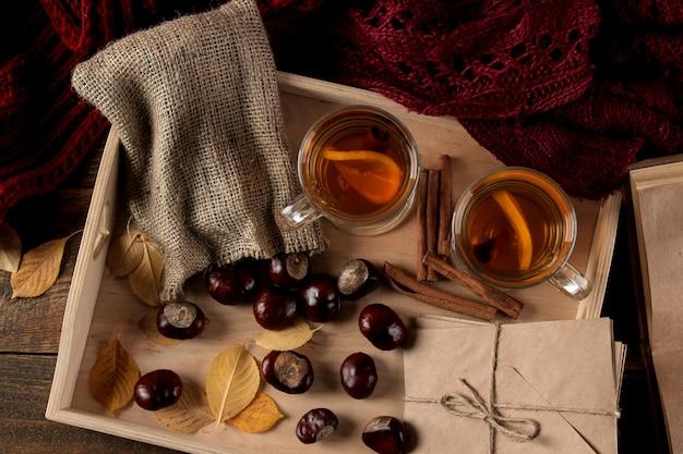 Herbstkomposition mit gelben blättern und büchern des heißen tees auf einem braunen holztisch.