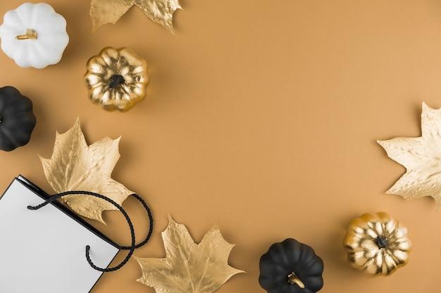 Herbstkomposition mit goldenen ahornblättern, dekorativen kürbissen und einkaufstasche