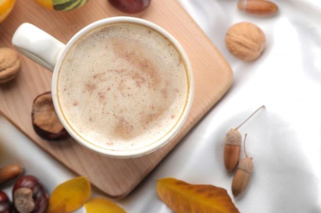 Herbstkomposition mit heißem kaffee und gelben blättern auf einem tablett auf dem bett. sicht von oben