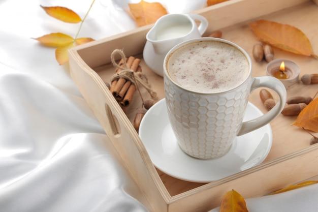 Herbstkomposition mit heißem kaffee und gelben blättern auf einem tablett auf dem bett.