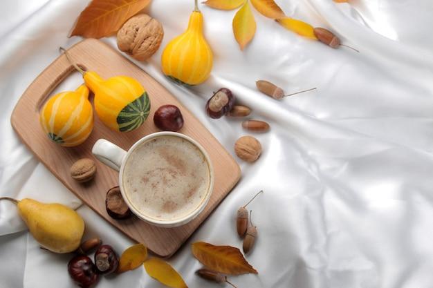 Herbstkomposition mit heißem kaffee und gelben blättern und dekorativen kürbissen auf einem tablett, auf einem bett. sicht von oben