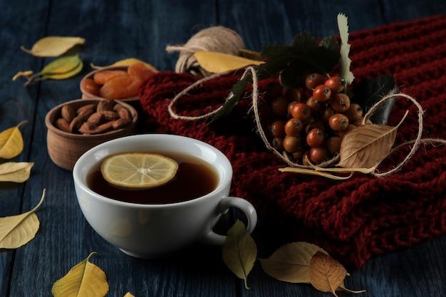 Herbstkomposition mit heißen teenussbeeren und herbstgelben blättern auf einem dunkelblauen holztisch