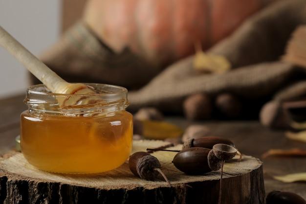 Herbstkomposition mit honignahaufnahme und eicheln auf einem holzständer auf einem braunen holztisch