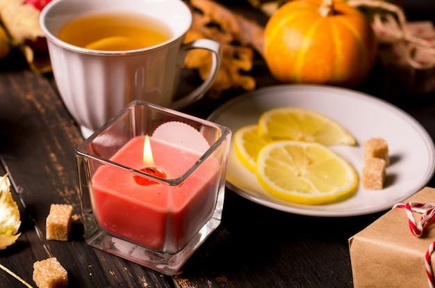 Herbstkomposition mit kerzen, kürbissen und herbstlaub, tasse tee auf dunklem rustikalem holztisch. thanksgiving und halloween-feiertag. konzept der herbstsaison. herbststillleben. flach legen, platz kopieren