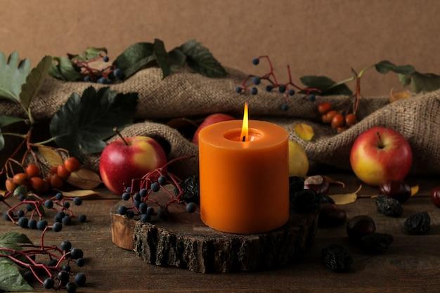 Herbstkomposition mit kerzen und herbstfrüchten und beeren und kastanien auf einem braunen holztisch