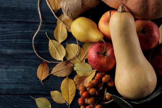 Herbstkomposition mit kürbis und herbstfrüchten mit äpfeln und birnen und gelben blättern auf einem dunkelblauen tisch. ansicht von oben