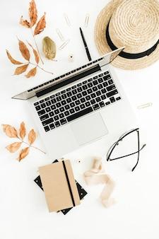 Herbstkomposition mit laptop, tagebuch, stroh und trockenem herbstlaub. flache lage, ansicht von oben