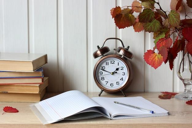Herbstkomposition mit offenem notizbuch, lehrbüchern und herbstlichen espenblättern auf dem tisch zurück zum schulinnenraum mit bronzewecker