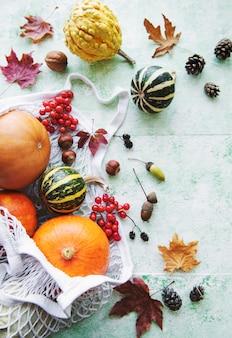 Herbstkomposition mit verschiedenen kürbissen in öko-string-tasche, thanksgiving-hintergrund.