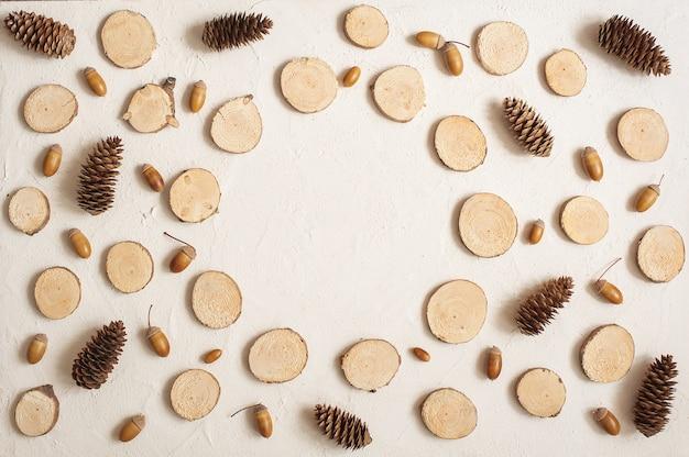 Herbstkomposition, rahmen aus tannenzapfen, eicheln und kleinen holzstümpfen.