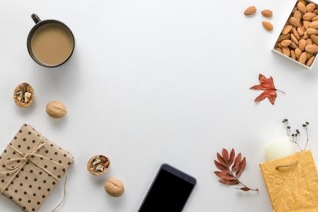 Herbstkomposition. tasse kaffee, sartphone, getrocknete blätter auf weiß