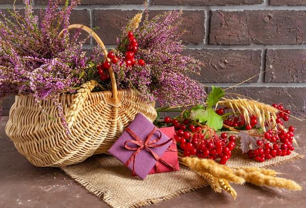 Herbstkomposition von heidekraut in einem weidenkorb viburnum weizenähren und geschenken stillleben