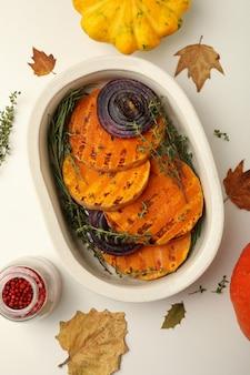 Herbstkonzept mit gebackenem kürbis auf weißem hintergrund.