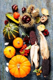 Herbstkonzept mit saisonalen früchten und gemüse auf holzbrett