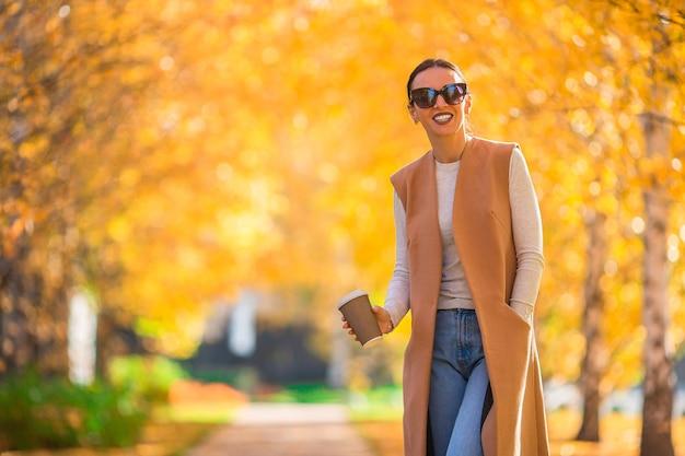 Herbstkonzept - schöne frau, die kaffee im herbstpark unter herbstlaub trinkt