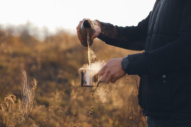 Herbstkonzeptheißer kaffee in der handeine tasse heiße schokolade in den händen im herbstheißer kaffee mit