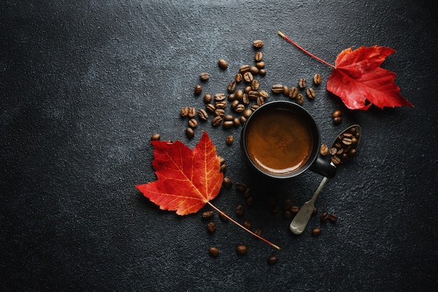 Herbstkonzepthintergrund mit herbstlaub und kaffee, der in der schale auf dunklem hintergrund serviert wird.