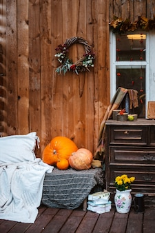Herbstkranz und kürbise auf hölzernem rustikalem hintergrund.