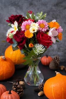 Herbstkürbisse und blumen auf dunklem hintergrund, warme und gemütliche komposition des herbstes