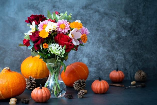 Herbstkürbisse und blumen auf dunklem hintergrund, warmes und gemütliches arrangement. kopieren sie platz für text
