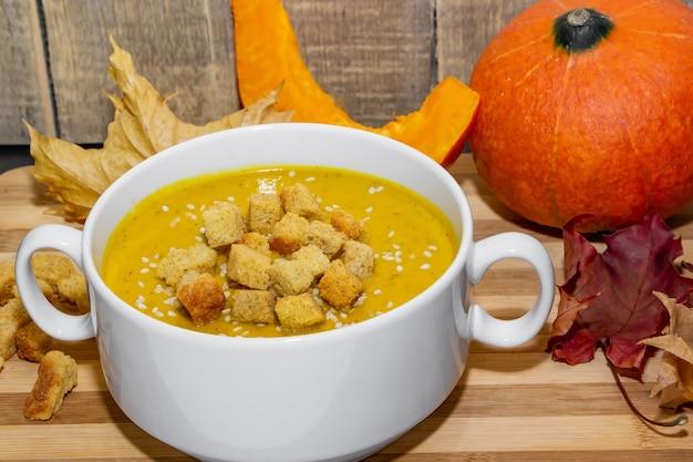 Herbstkürbissuppe mit sesam auf einem hölzernen hintergrund. kürbispüreesuppe mit crackern und sesam auf einem hintergrund des herbstlaubs