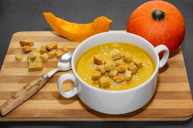 Herbstkürbissuppe mit sesam auf einem hölzernen hintergrund. suppe in einem teller und kürbisscheiben auf einem hölzernen hintergrund