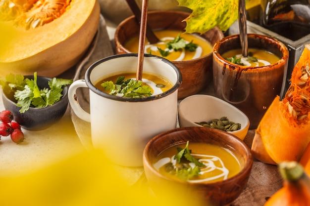 Herbstkürbissuppenpüree mit sahne in den schalen, die herbstlandschaft. gesundes veganes lebensmittelkonzept.