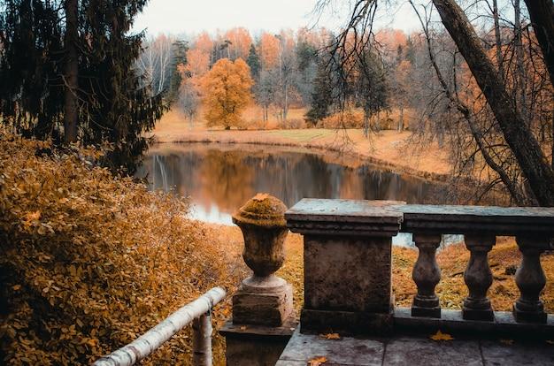 Herbstlandschaft auf einem wald und einem see mit einem alten balkon.