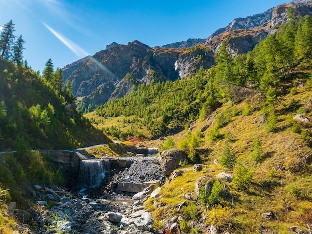 Herbstlandschaft im alpental, bach, der zwischen wiesen und lärchenwald fließt. bergblick, herbstliche farben, klarer blauer himmel.