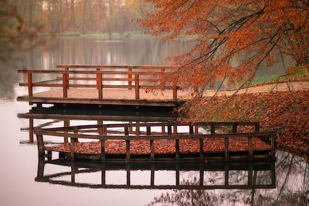 Herbstlandschaft im stadtpark holzboot auf dem wasser