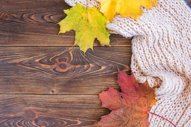 Herbstlaub auf dunklem holzbrett
