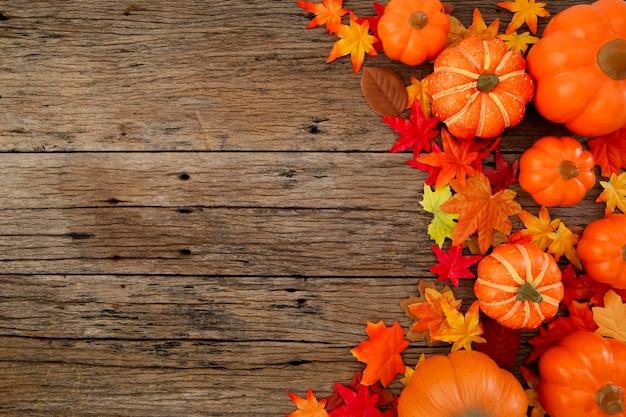 Herbstlaub auf hölzernem hintergrund