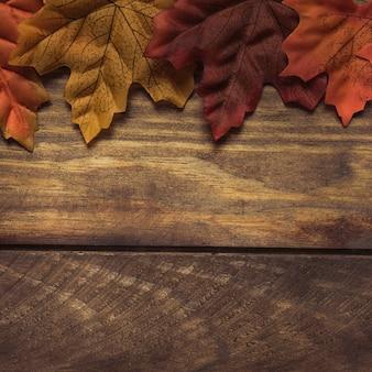 Herbstlaub auf rauen hölzernen Planken