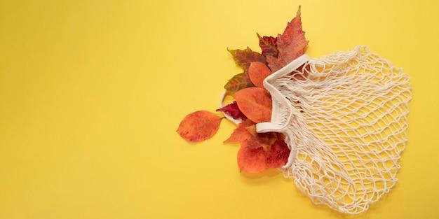 Herbstlaub in öko-mesh-tasche auf leuchtend gelbem hintergrund.