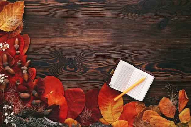 Herbstlaub, kekse und notizbuch aus papier auf holz