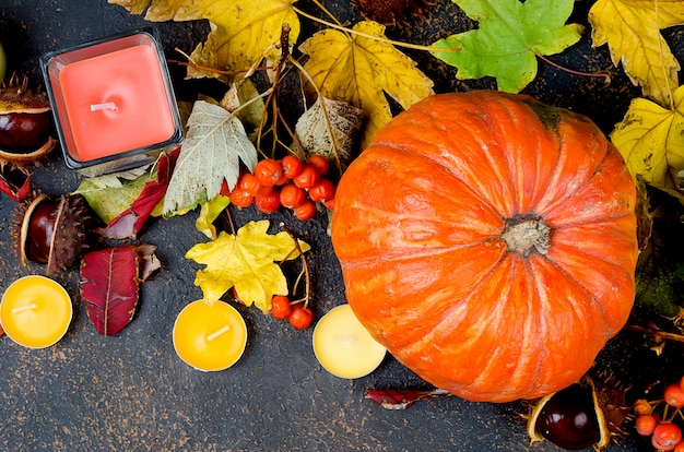 Herbstlaub, kürbis, kastanien, kerzen auf einer dunkelheit