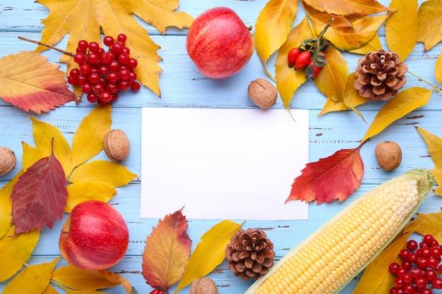 Herbstlaub mit beeren und gemüse auf blau. herbst komposition mit karte