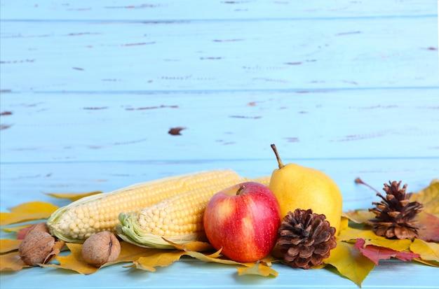 Herbstlaub mit beeren und gemüse auf blau