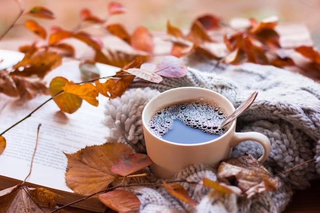 Herbstlaub mit einer tasse kaffee und einem offenen buch