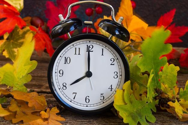 Herbstlaub mit wecker auf dem tisch