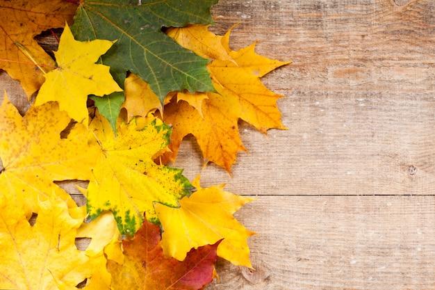 Herbstlaub über hölzernem hintergrund