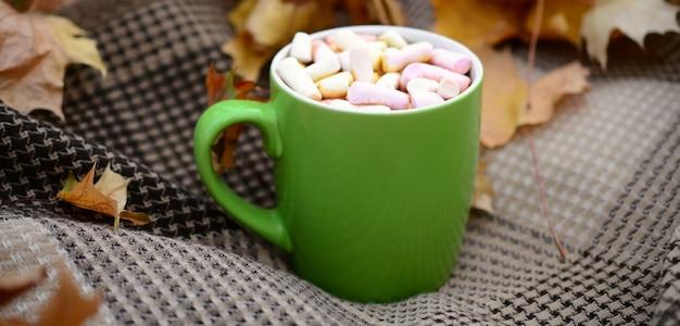 Herbstlaub und heiße dampfende tasse kaffee