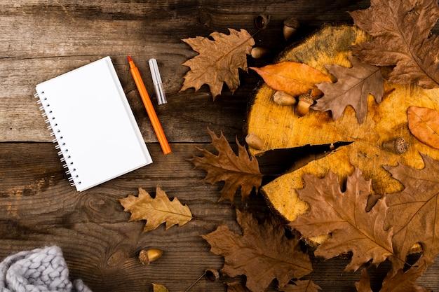 Herbstlaub und notizbuch auf hölzernem hintergrund