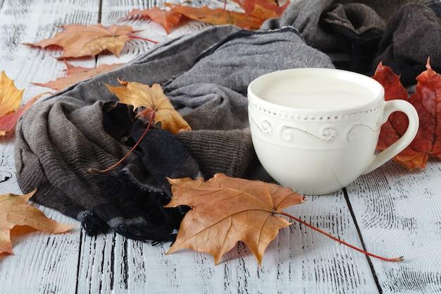 Herbstlaub und schwarze kaffeezusammensetzung. kaffeetasse am verwitterten rustikalen hölzernen hintergrund. herbst-heißgetränkekonzept