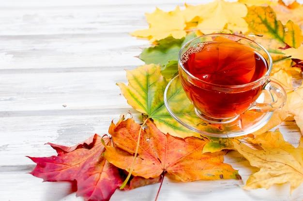 Herbstlaub und tasse tee auf holztisch