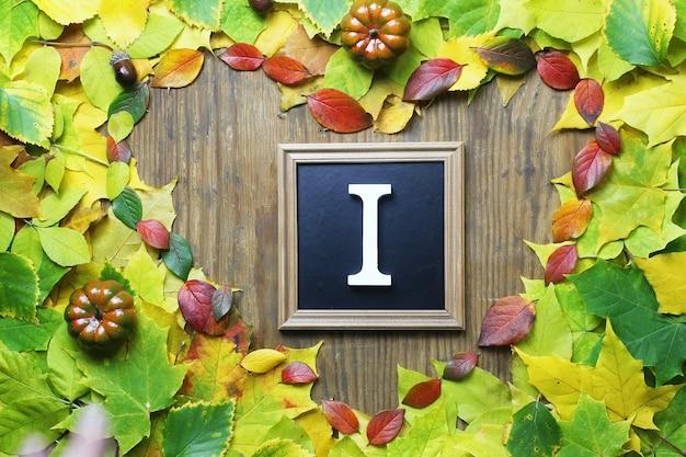 Herbstlaubhintergrund in form des herzens auf holztisch