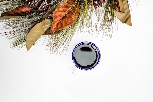Herbstlaubmuster mit kaffeetasse auf weißem hintergrund