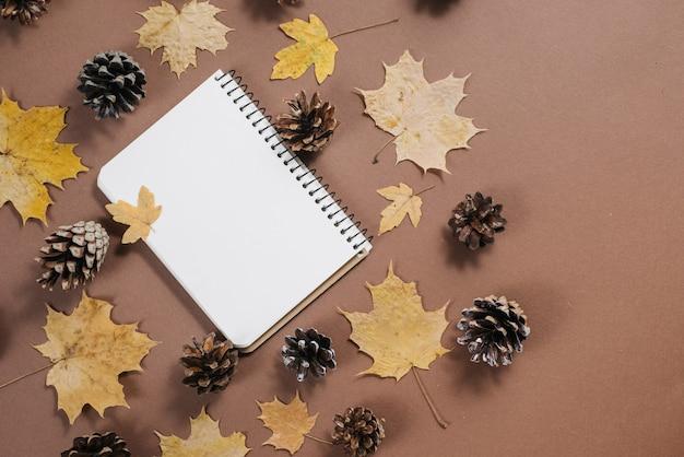 Herbstlaubmuster mit stößen und notizbuch auf braunem hintergrund.